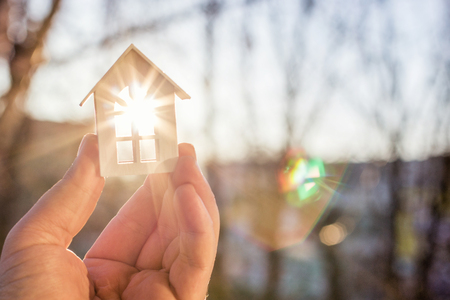 House in hand in the rays of the sun. The concept of protection of property. Stock Photo