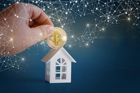 Investering in onroerend goed. Hand met munt en huis. Stockfoto