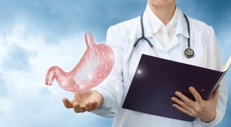 Doctor gastroenterologist shows the stomach against the sky. Stockfoto