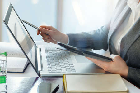 Business woman showing a growth chart on a laptop at the table. Stock Photo