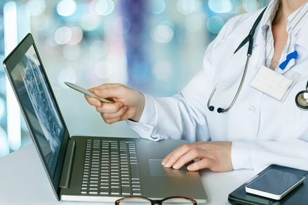 Doctor looks at the laptop at the table. Stock Photo