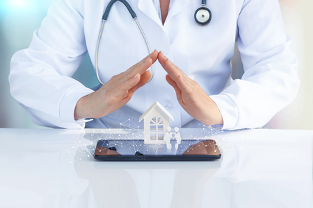 Doctor at the table with his hands to protect the icon the family and home. The concept of health insurance of the family.