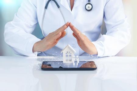 Médecin à table avec ses mains pour protéger l'icône de la famille et de la maison. Le concept d'assurance maladie de la famille.
