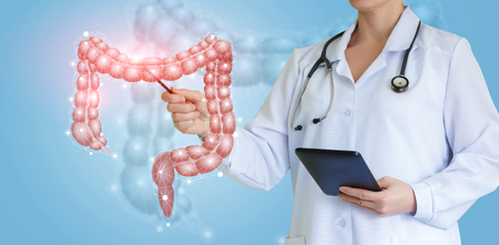 Doctor shows colon on virtual screen over blue background. Stockfoto