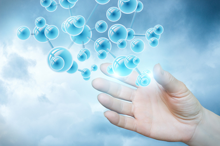 Struktura cząsteczki w ręku na jasnoniebieskim tle.