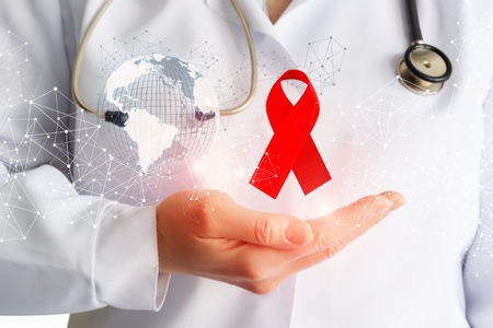 Medic shows red aids ribbon on hand . Concept design.