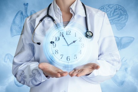 Doctor shows the clock on the background of internal organs and the sky. Banco de Imagens
