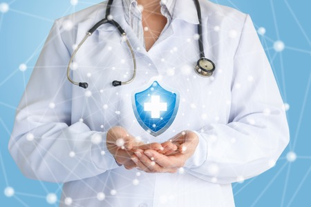 Doctor shows the symbol of protection of health on a blue background.