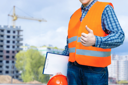 Builder shows quality construction on blurred background . Stock Photo