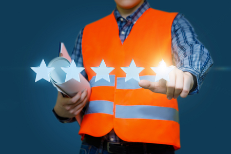 Builder clicks on the fifth star. The concept of assessment. Stockfoto - 97998560