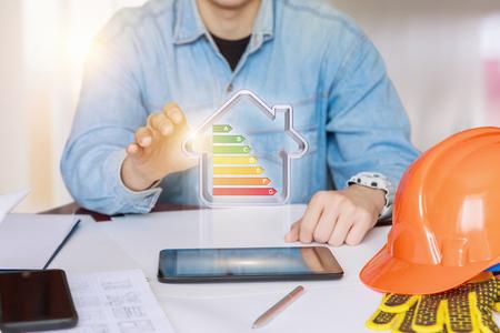 Ingeniero que muestra una casa modelo de eficiencia energética en la tableta.