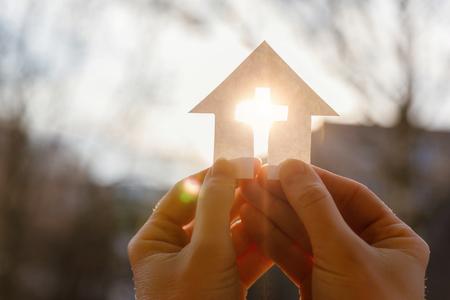 Ręka z domem z papieru i krzyżem na tle wschodu słońca.