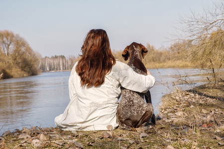 Dog and woman sitting arm in arm on the river Bank. Concept of friendship. Stock Photo