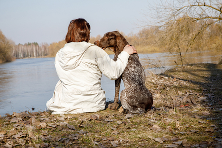 Woman with a dog sitting on the Bank of the river. The concept of friendship.