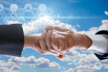 Handshake on the background of sky with clouds. The concept of cooperation. Stock Photo