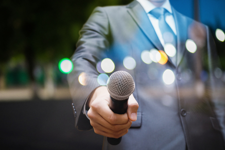 Speaker holds out the microphone on blurred background city.