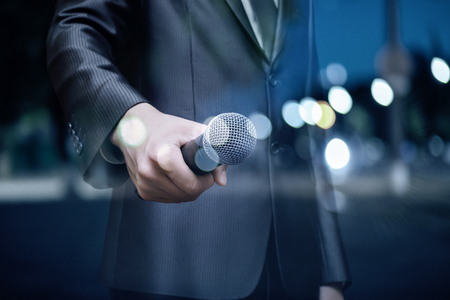 Speaker with the microphone on a blurred background of an evening city. Stock Photo