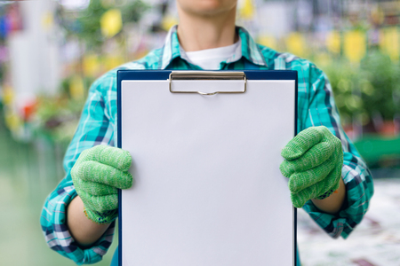 Worker shows check list on blurred background. Stock Photo