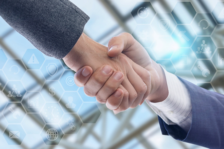 Handshake of two businessmen on blurred background. Concept of cooperation and agreement.