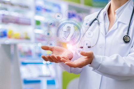 Pharmacist shows in the hands of a question mark on the background of the pharmacy.