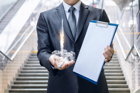 concept of start up and career growth.Businessman with documents to be signed with a soaring rocket in the background of the stairs.