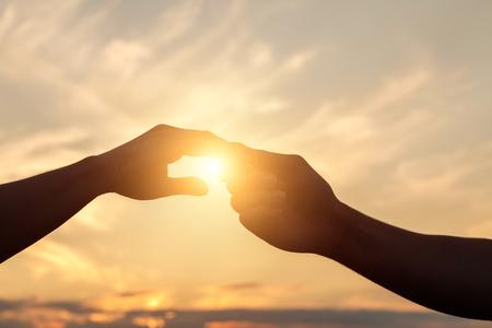 Händchenhalten im Hintergrund des Sonnenuntergangs.