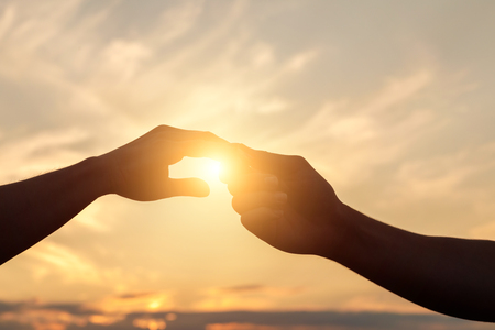 Holding Hands in the background of the sunset.