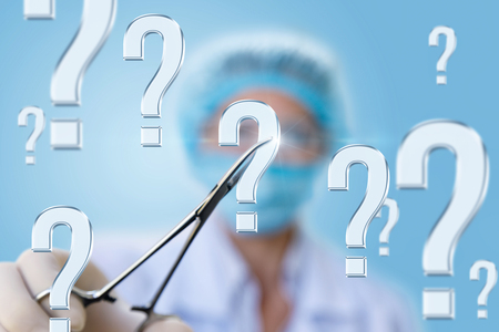 A doctor in the clamp holding the question mark on blurred background.