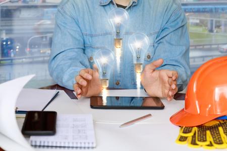 Builder montre les idées sur la tablette assise à la table.