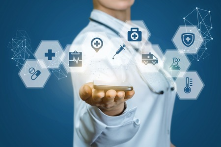 Doctor shows icons of medical care on a blue background. Stock Photo
