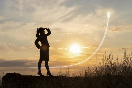 Businesswoman looking at successful profit growth at sunset.