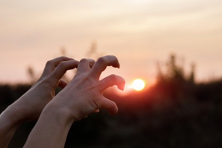Hand gestures of the monster on the background of sunset. Stock Photo