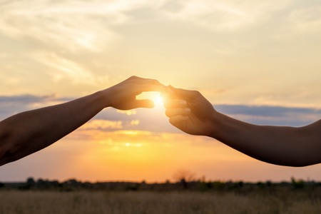 Hands contact each other in the background of the sunset.