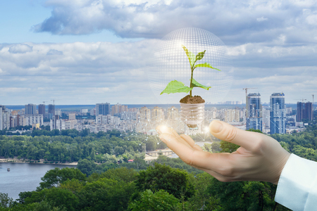 Hand showing sprout in the bulb on the background of the city. Green energy concept. Stock Photo