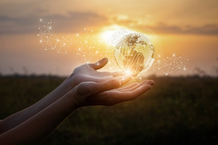 Hands show the global network at sunset. Stock Photo