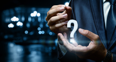 Question mark in the hand of businessman over city background. Concept answers to the questions. Stock Photo
