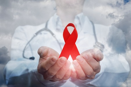 A medical worker showing the aids red ribbon against the sky.