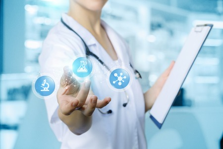A doctor with a stethoscope around her neck is showing a digital system consisting of pharmaceutical icons symbolizing the increase in new drugs development at the lab room background.