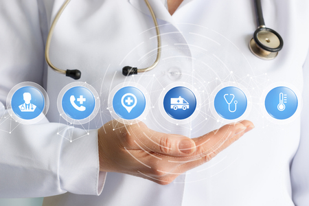 A doctor with a stethoscope is holding a structure of small spheres with medical symbols inside. The concept is the interaction of different medical trends. Stock Photo