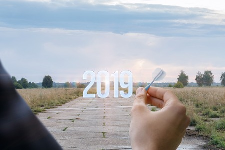 A man with a dart in his hand is standing opposite the numbers of coming year at the wide road background. The concept is the opportunities and perspective of coming year