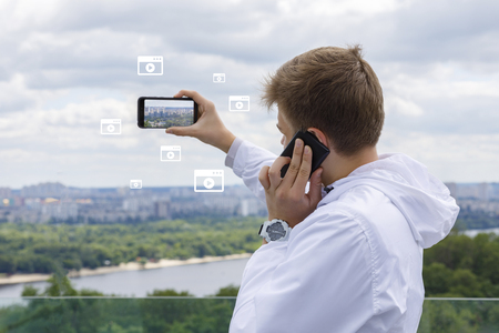A young man is using two devices for communication and making photos at the city landscape with large river background. The concept is the role of technologic progress in everyday life.