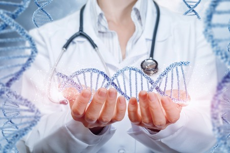 A doctor with a stethoscope is holding a dna line in her hands with the same chains on each side. The concept is the impact of modern medicine on future generations. Archivio Fotografico