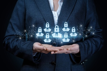 A businesswoman is holding a group of human figures icons with padlocks instead of their heads. The financial security system principle.
