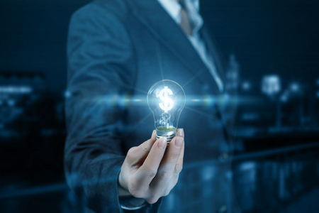 A businesswoman is holding a shining lightbulb with a currency unit inside at the dark background. The concept is the profitable financial idea.