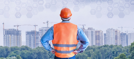 An engineer in the uniform is standing with his back and looking at the skyscrapers construction ground.The concept is the perspective of building industry development.