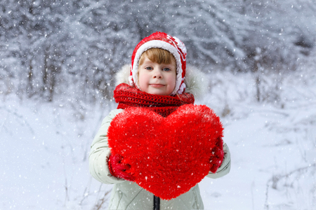 A little cute girl in bright clothes is showing a huge red heart at the winter landscape background. The concept is the St.valentine Day Celebration. Banque d'images