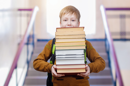 A pupil with a schoolbag behind his back is going downstairs keeping a pile with of many books in his hands. The concept is the importance of education.