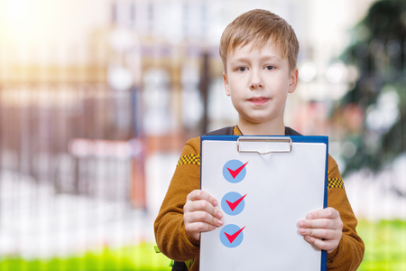 A schoolboy is standing at educational establishment blurred background and showing a plane table with a list of done tasks. Foto de archivo - 114592491