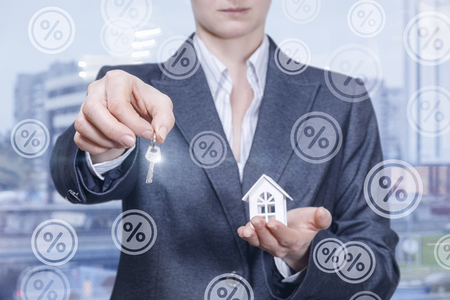 A businesswoman in suit is holding a key in one hand and a house model on her palm surrounded by percents icons at the big city background. The concept is financial mortgage principle. Stok Fotoğraf