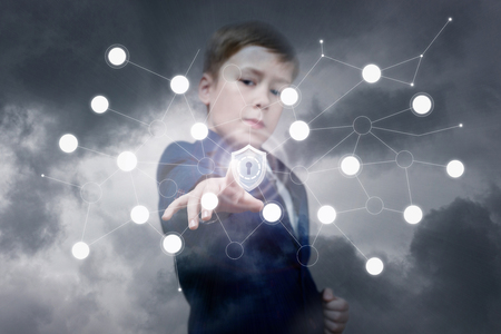 A confident officially dressed teenage child is pushing a shield inside a digital network system at the grey sky background. The concept is database and network protection and security. Archivio Fotografico - 116825069